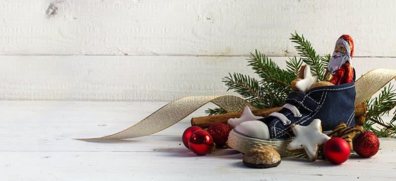 A sapata das crianças encheu-se com os doces, as cookies e o decorat do Natal fotos de stock