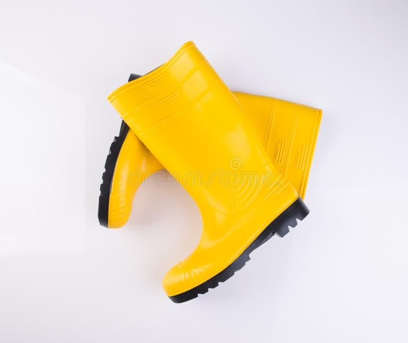 sapata ou botas de borracha da cor amarela em um fundo fotografia de stock