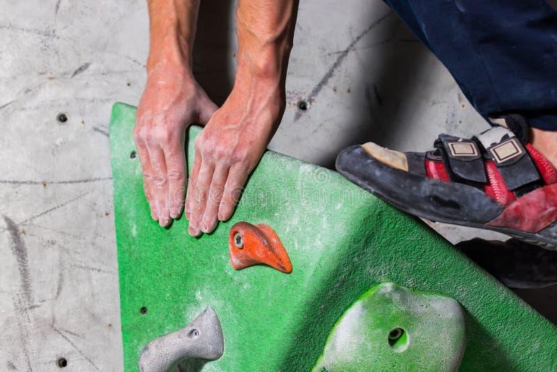 Sapata rochosa em uns suportes minúsculos, exíguos da cilada com a ponta da peúga no close-up na parede de escalada na sala foto de stock