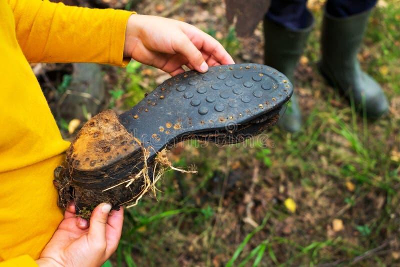 Sapata velha do soldado da exibição da criança da segunda guerra mundial que encontrou na floresta imagem de stock