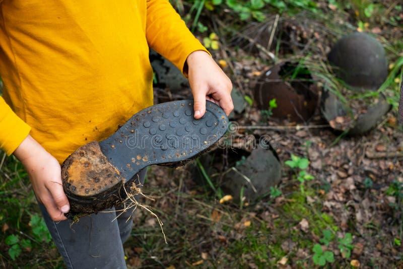 Sapata velha do soldado da exibição da criança da segunda guerra mundial que encontrou na floresta imagens de stock royalty free