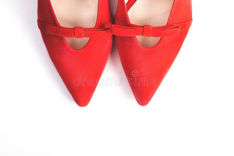 Sapatas alto-colocadas saltos fêmeas vermelhas no fundo branco Sapatas luxuosas do partido imagens de stock royalty free