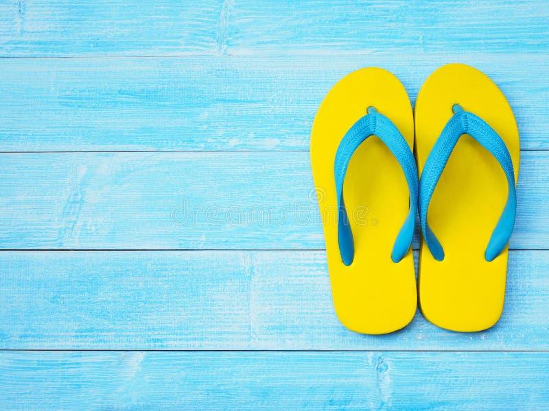 Sapatas amarelas do falhanço de aleta no fundo de madeira azul imagens de stock royalty free