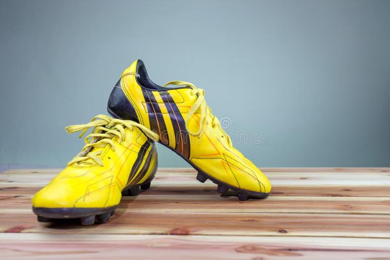 Sapatas amarelas velhas colocadas em uma placa de madeira, luz suave cinzenta do futebol do fundo fotografia de stock