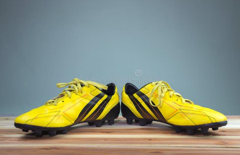 Sapatas amarelas velhas colocadas em uma placa de madeira, luz suave cinzenta do futebol do fundo imagem de stock royalty free