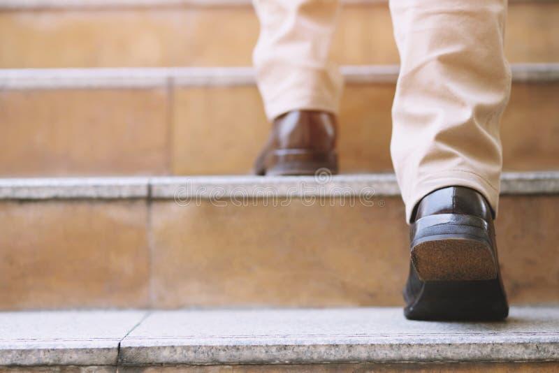 Sapatas ascendentes próximas dos pés de ir de passeio do piso da pessoa nova do homem de negócio um acima as escadas na cidade mo fotografia de stock