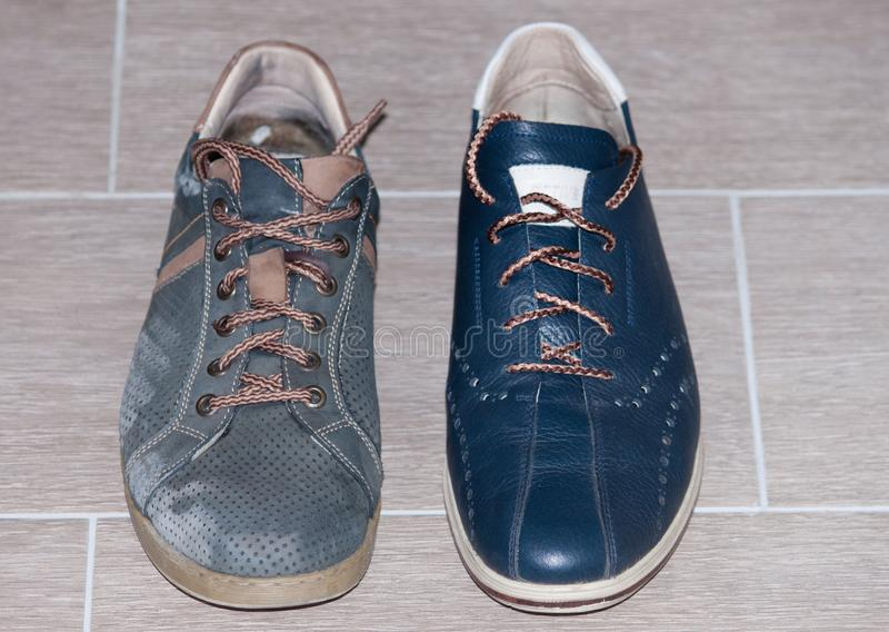 Sapatas azuis novas e velhas no assoalho fotografia de stock