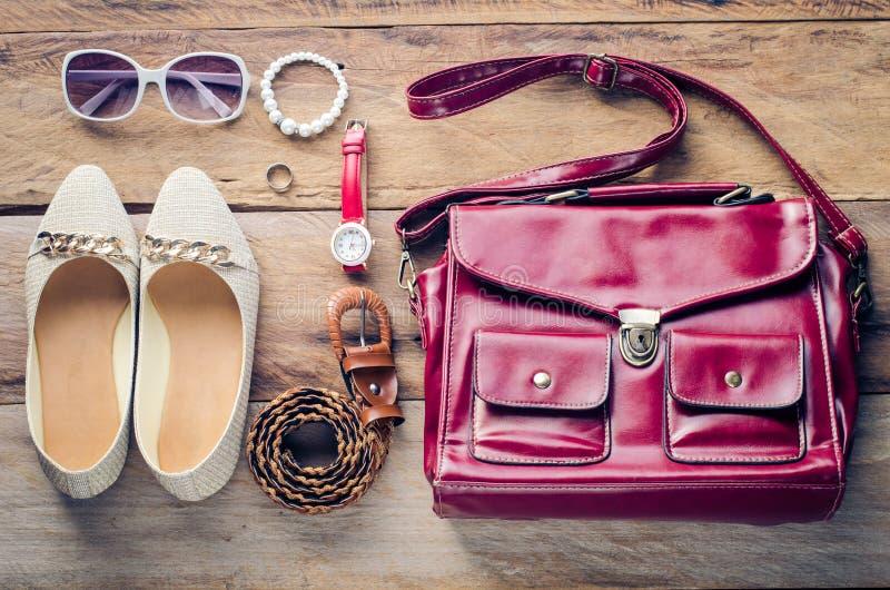 Sapatas, bolsas, acessórios para mulheres, colocados em um assoalho de madeira foto de stock