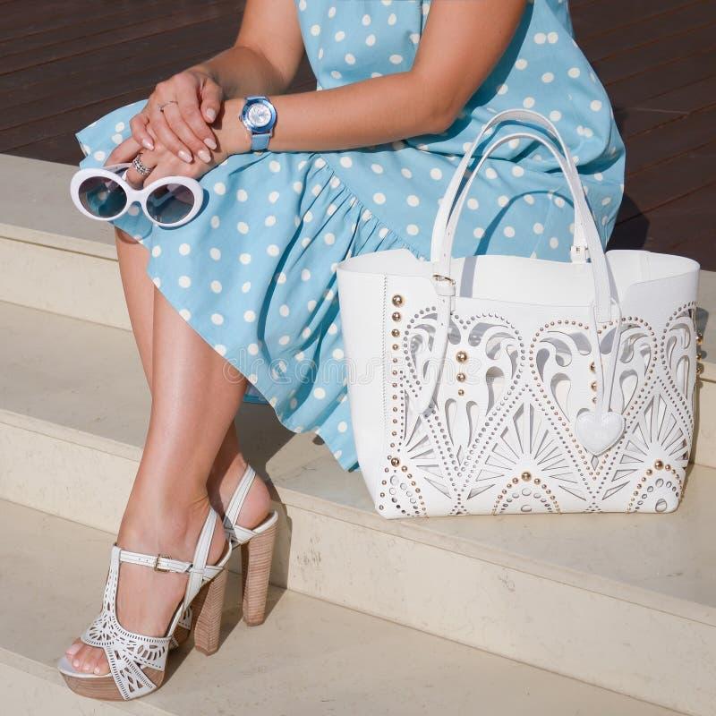Sapatas bonitas e elegantes no pé do ` s das mulheres Mulher Acessórios à moda das senhoras sapatas brancas, saco, vestido azul d foto de stock royalty free