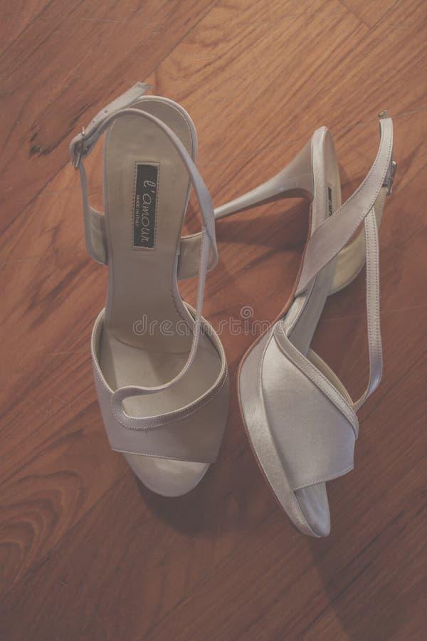 Sapatas brancas do casamento na madeira imagem de stock