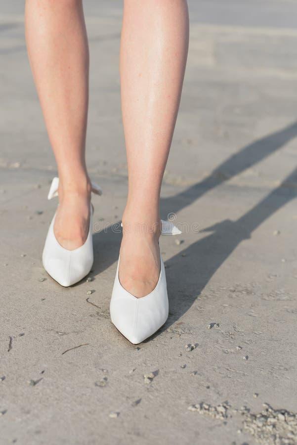 Sapatas brancas nos pés da menina Os pés nas sapatas são close-up Uma menina em sapatas elegantes anda através da cidade asfalto imagens de stock