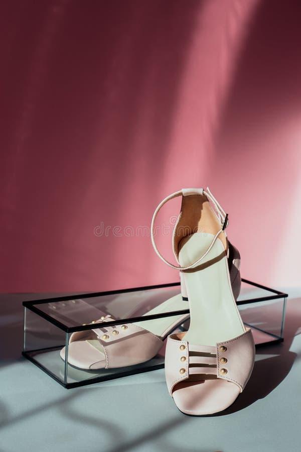 Sapatas brilhantes com salto pequeno, fundo da cor fotografia de stock royalty free