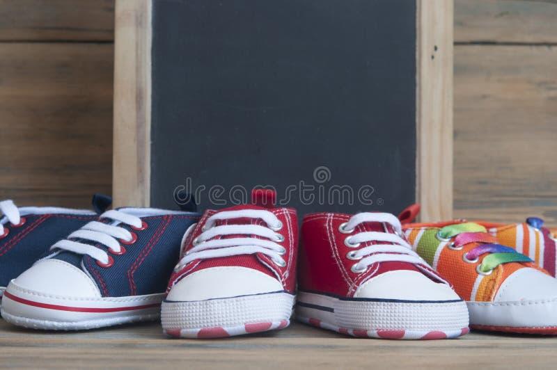 Sapatas coloridas da criança no fundo de madeira imagem de stock royalty free