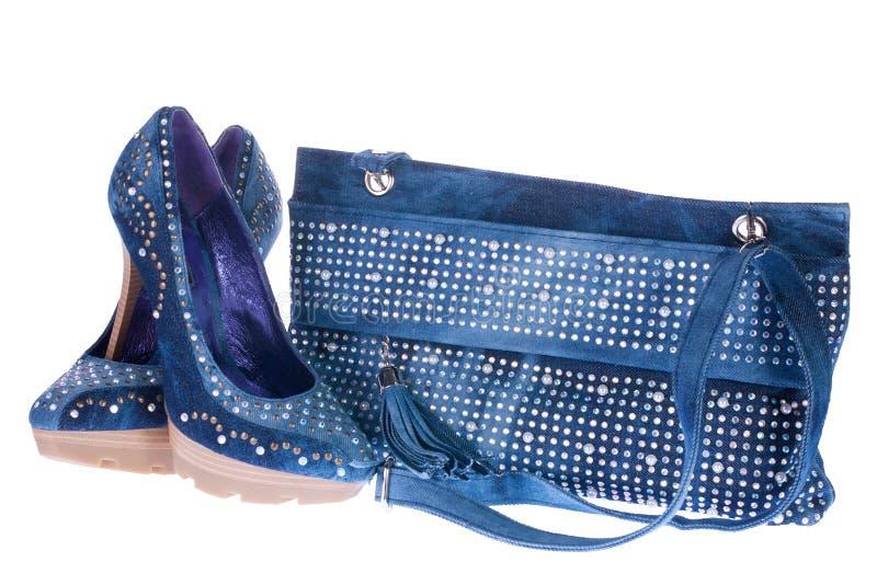 Sapatas da sarja de Nimes das mulheres e saco de embreagem da sarja de Nimes imagem de stock