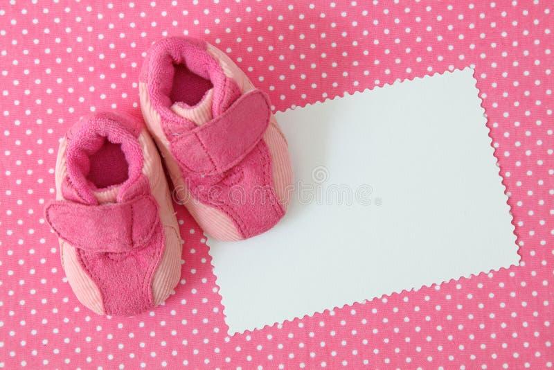 Sapatas de bebê cor-de-rosa e nota em branco fotografia de stock