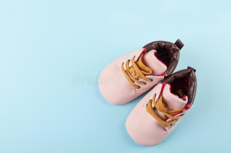Sapatas de beb? cor-de-rosa no fundo azul Forma para o conceito do fundo das crian?as Vista da parte superior imagens de stock royalty free