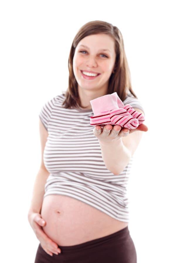 Sapatas de bebê da terra arrendada da mulher gravida imagens de stock