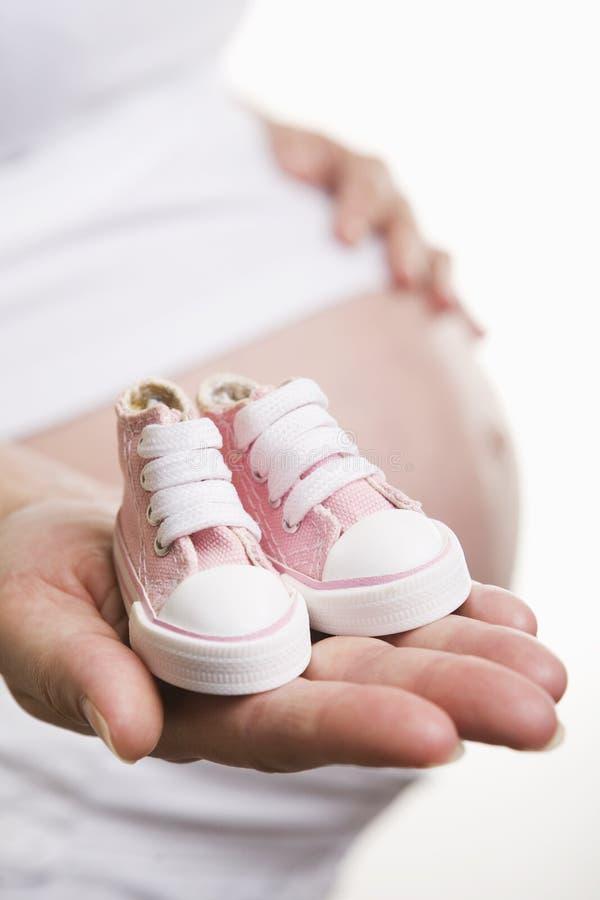 Sapatas de bebê da terra arrendada da mulher gravida fotos de stock