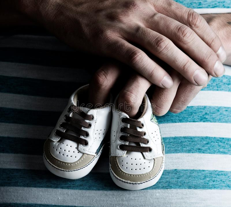 Sapatas de bebê da terra arrendada da mulher gravida em sua barriga imagem de stock royalty free