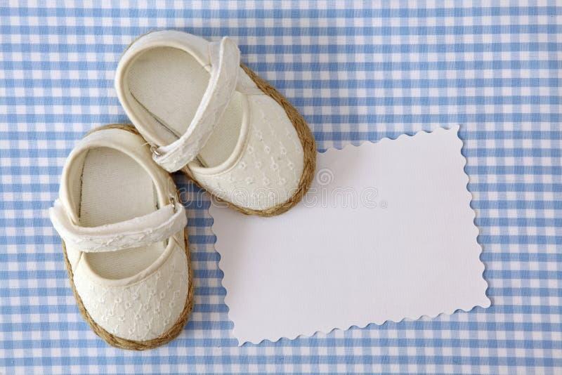 Sapatas de bebê e nota em branco fotografia de stock