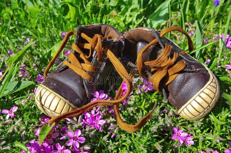 Sapatas de bebê na grama imagens de stock