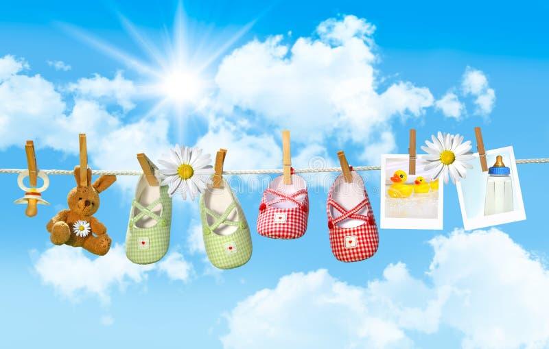 Sapatas de bebê, pacifier e urso de peluche no clothesline foto de stock