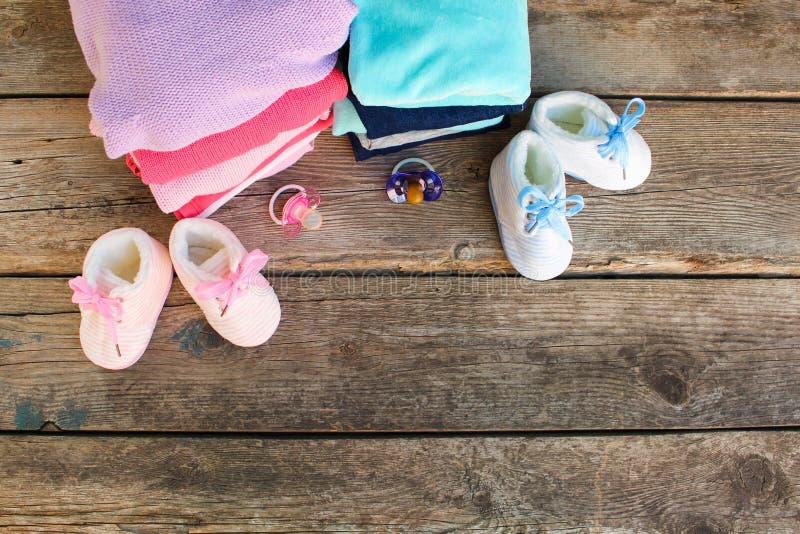 Sapatas de bebê, roupa e chupetas rosa e azul imagens de stock