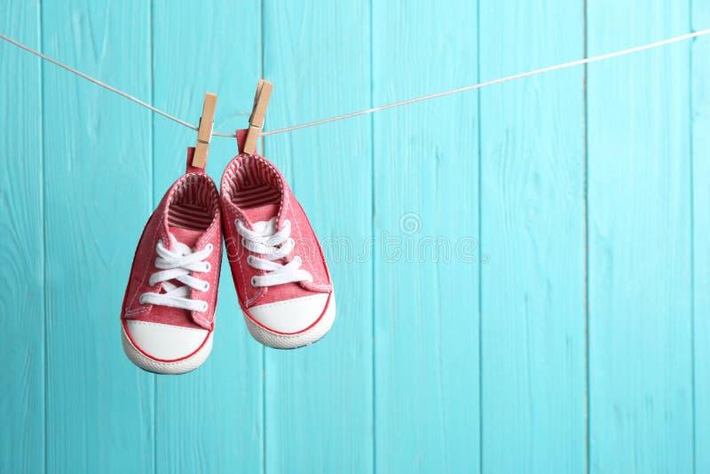 Sapatas de beb? na linha da lavanderia contra o fundo de madeira da cor Acess?rios da crian?a fotografia de stock royalty free