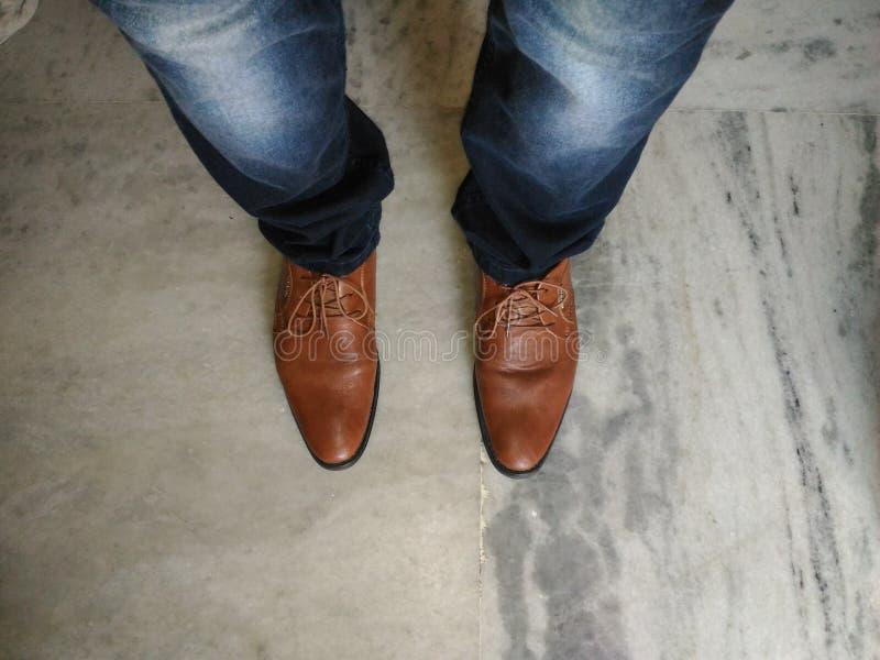 Sapatas de couro de calças de ganga e de Brown imagens de stock royalty free