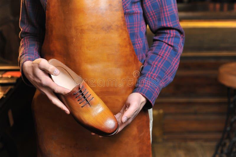 Sapatas de couro nas mãos do mestre foto de stock