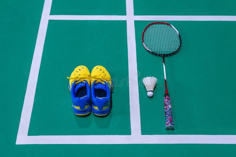 sapatas do badminton com peteca e raquete na corte fotografia de stock royalty free