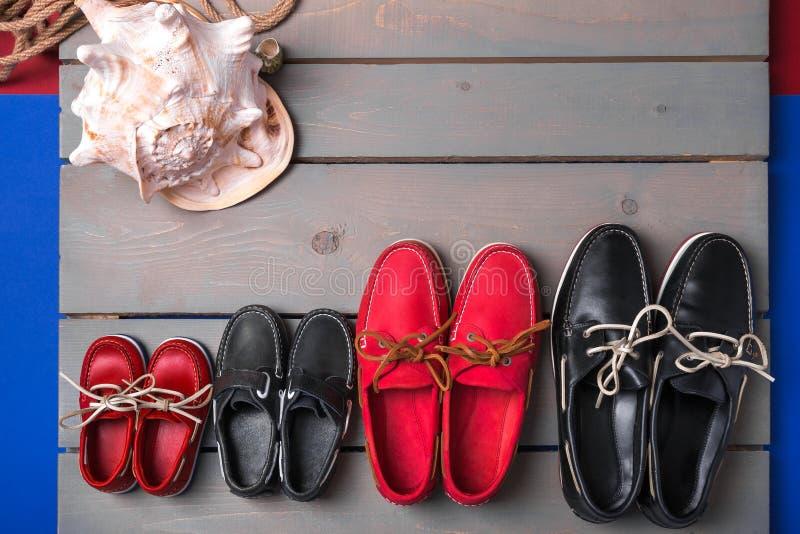Sapatas do barco da família no fundo de madeira Quatro pares de mesa cinzenta vermelha e preta com shell da corda Vista superior, fotografia de stock