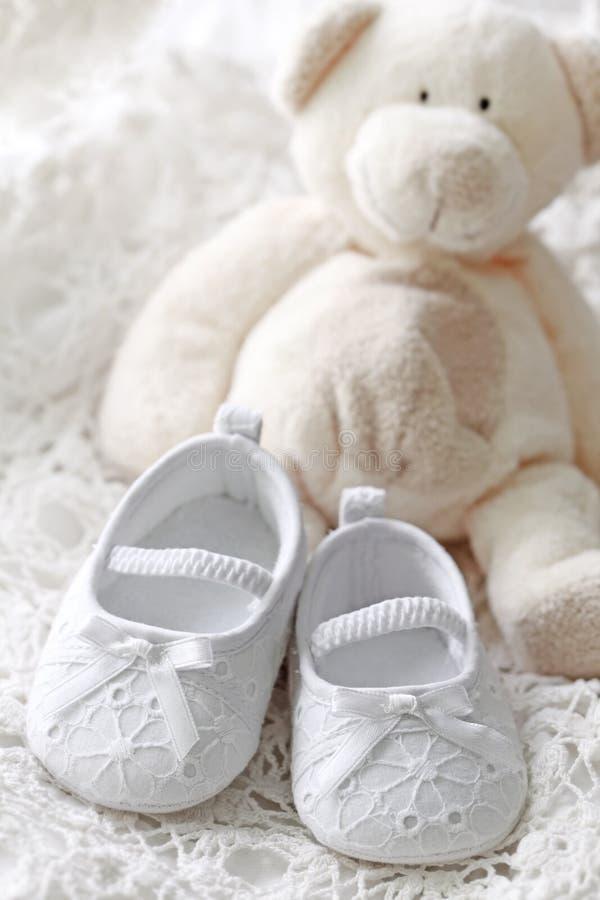 Sapatas do bebé e urso de peluche imagem de stock royalty free