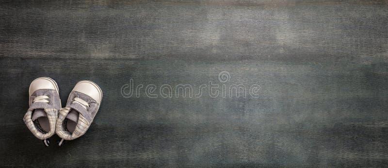 Sapatas do bebê no fundo de madeira azul, bandeira fotografia de stock