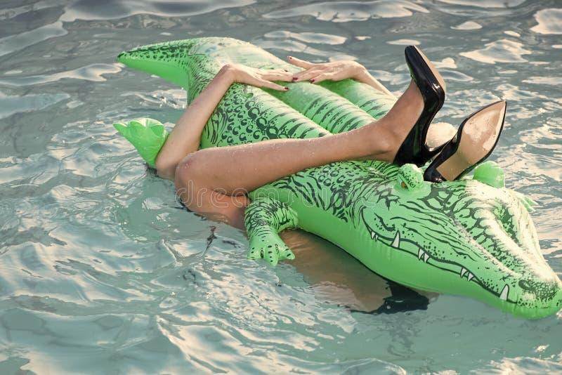 Sapatas do couro do crocodilo mulher no mar com colchão inflável Colchão fêmea da posse dos pés na piscina Forma imagem de stock
