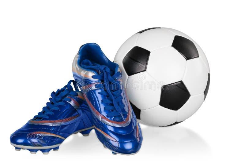 Sapatas do futebol e bola de futebol azuis e brancas fotografia de stock royalty free