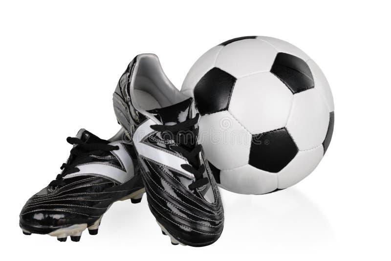 Sapatas do futebol e bola de futebol preto e branco fotografia de stock royalty free