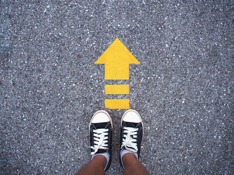 Sapatas do preto da sapatilha de Selfie na estrada concreta com li amarelo da seta fotos de stock