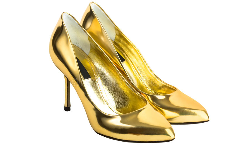 Sapatas do salto elevado das mulheres do ouro foto de stock