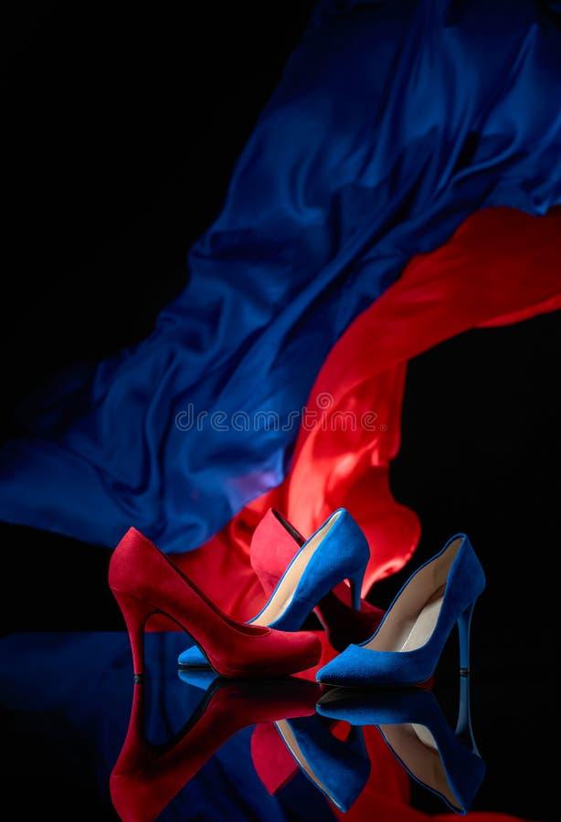 Sapatas do veludo de algodão das mulheres azuis e vermelhas em um fundo reflexivo preto imagem de stock