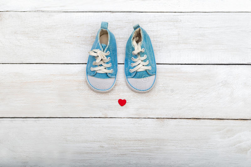 Sapatas dos azuis bebê no fundo de madeira Configuração lisa foto de stock