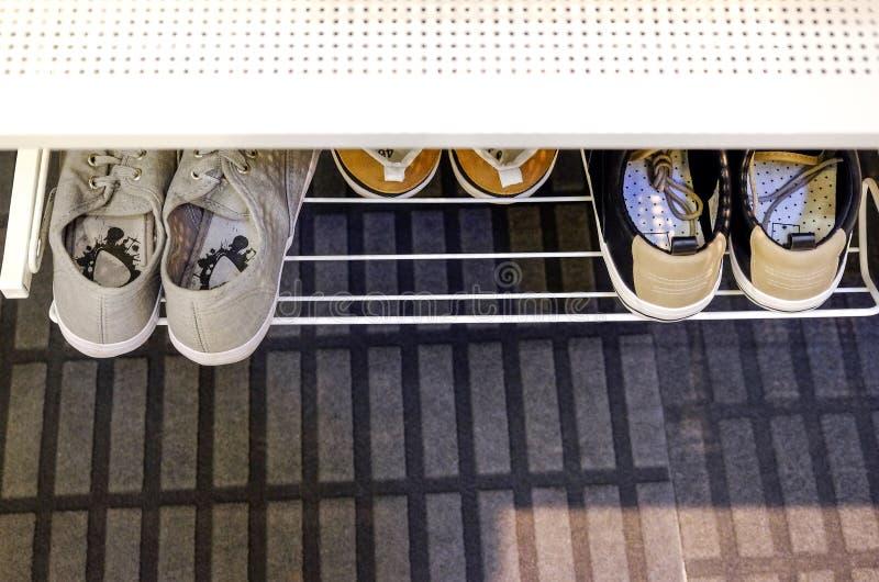 Sapatas dos esportes em um suporte no corredor foto de stock