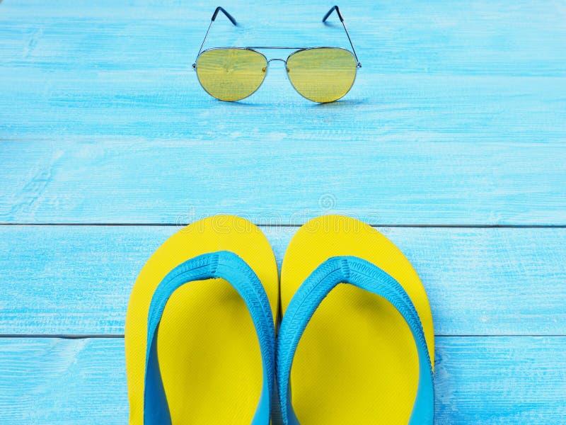 Sapatas e óculos de sol amarelos do falhanço de aleta no fundo de madeira azul imagem de stock royalty free
