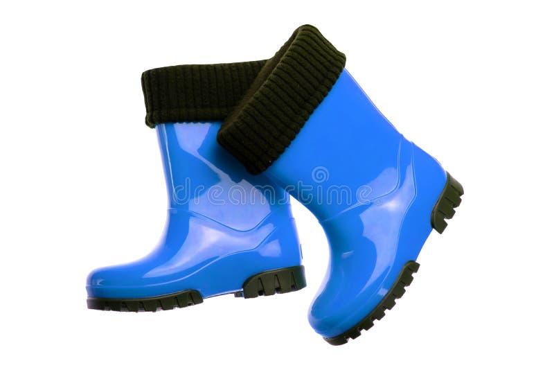 Sapatas e botas das crianças O close up de botas de borracha azuis de um par é imagem de stock