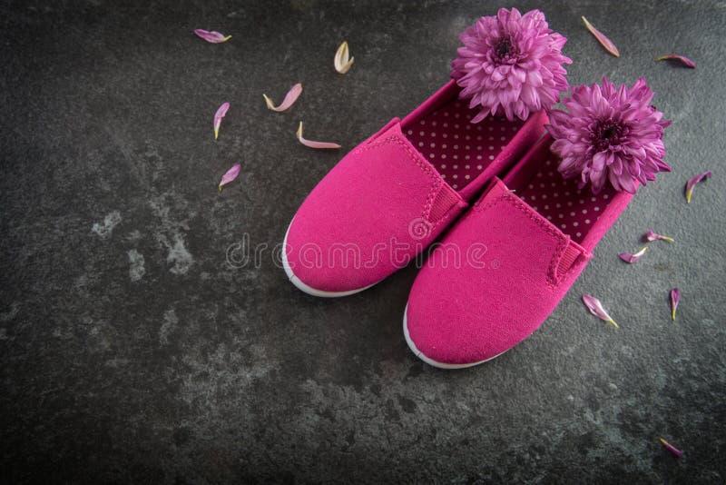 Sapatas e flores cor-de-rosa da criança em um fundo escuro da ardósia, conceito I fotografia de stock