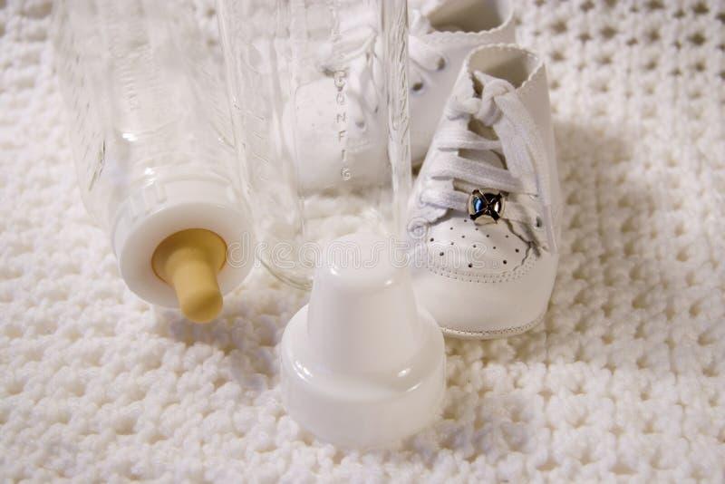 Sapatas e frasco de bebê fotografia de stock