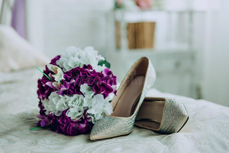 Sapatas e ramalhete do casamento com as flores brancas e roxas imagem de stock