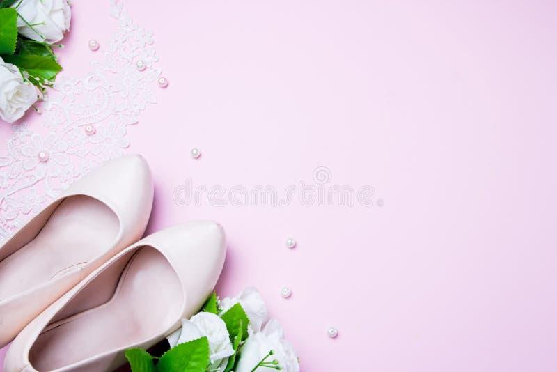 Sapatas e ramalhete do casamento que encontram-se no fundo cor-de-rosa Fim acima Configura??o lisa Vista superior imagens de stock