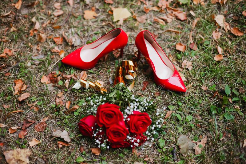 Sapatas e ramalhete vermelhos do casamento de rosas vermelhas na grama Detalhes nupciais imagens de stock