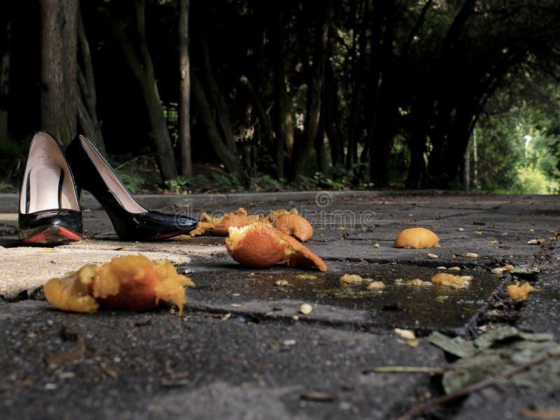 Sapatas envernizadas pretas das mulheres com os saltos na rua perto do mandarino esmagado foto de stock royalty free
